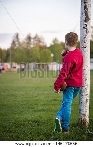 Little soccer player standing in the goalposts defending the the line and ready to throw a football. Cute kid boy standing as goalkeeper on a sportsfield on a sunny day. Sport activities for children