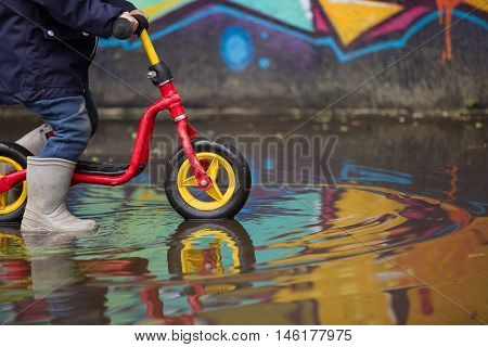 Little child in grey rubber boots cycling after rain.Toddler in a pair of grey rubber boots in a big puddle with grafiti wall reflection. Fun after rain. Boy on the bike on the street.