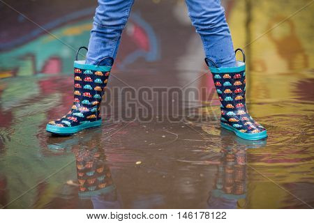 Kid boy in funny rubber boots standing in the puddle in the street after rain. Pair of colorful rubber boots in a big puddle with graffiti refclections. Boy having fun after rain. Outdoor.