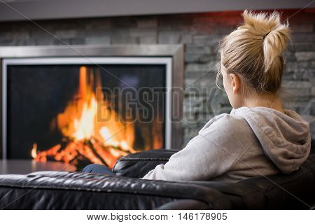 Back view on blond woman sitting at the fire place and watching the fire. Woman in the living room. Fire screen - artificial fireplace. Woman waiting for the flight in the airport.