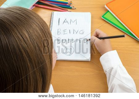 An Horizontal image / poster covering the Social Issues of child abuse schoolchild in uniform at a desk asking for help by a written message saying I am being bullied with a sad face . Room for copy space and text