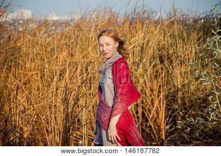 Red-haired woman with a red shawl in the light of the setting sun
