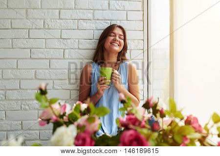 Young girl is genuinely happy while sitting on the window-sill and enjoying a sunny summer day