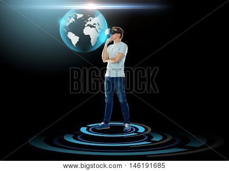 3d technology, augmented reality, gaming, cyberspace and people concept - happy young man with virtual reality headset or 3d glasses and looking at earth globe hologram over black background