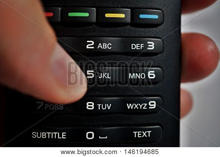 Male hand pressing numerical keyboard in the black remote control as a symbol of choice and home entertainment when watching television