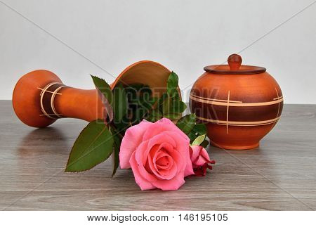 Capsize flower vase with roses. The vase is a wooden base.