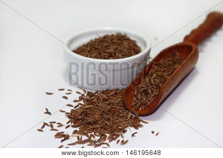 Caraway seeds in a small ceramic cup on a white background
