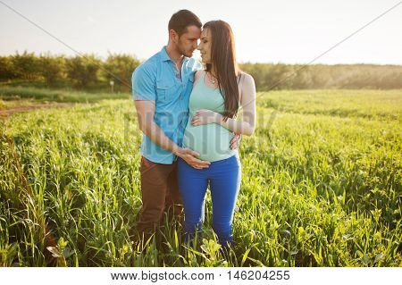 Happy Pregnant Couple At Garden On Magestic Sunset