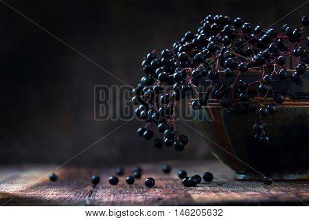 Black elderberries bunch (Sambucus nigra) in an old clay bowl and some berries on a rustic wooden table against a dark background with copy space low key vintage still life closeup with selected focus and extremely narrow depth of field