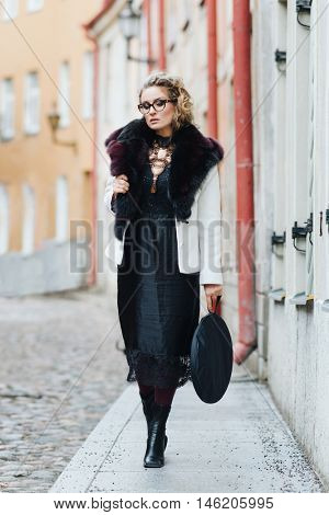 Gorgeous woman dressed in luxury clothes walking in the old town.