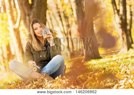Portrait of young blonde Caucasian happy woman, drinking coffee, sitting outdoors in park on sunny autumn day. Copy space, medium retouch, vibrant colors