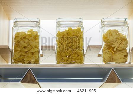 Different kinds of pasta in glass jars on the wooden shelf