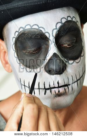 closeup of a young man making up himself as a mexican calaveras