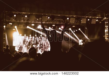 Black silhouette of young girl on rock concert, openair fest party