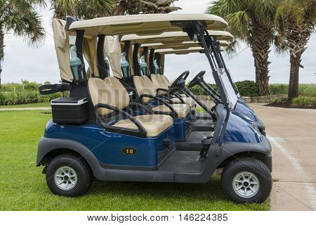 New clean golf course carts cars at luxury resort sport venue in neat line row