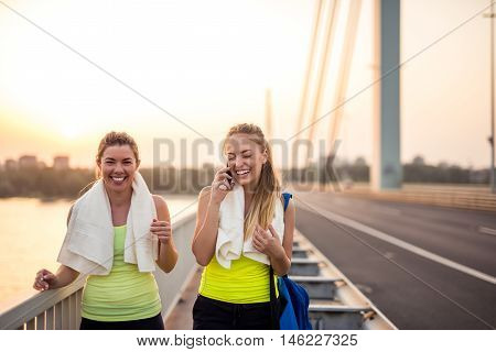 Two friends training together outdoors on the bridge.