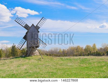 Wooden windmill on green field and blue sky background
