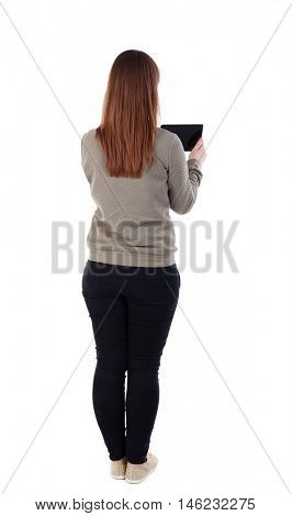back view of standing young beautiful woman using a mobile phone. girl watching. girl in a gray jacket's back and reading e-books.