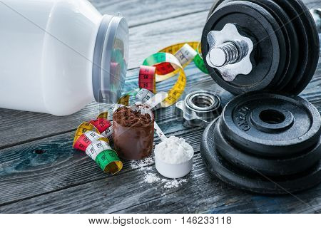 Classic Dumbbell With Protein Powder On Rustic Wooden Table