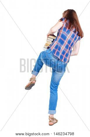 Girl carries a heavy pile of books. Girl in plaid shirt stands with his back knee keeping a stack of books