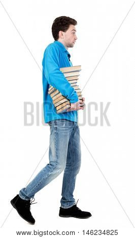 side view of going man carries a stack of books. curly-haired student in a blue warm jacket carries books. side view.