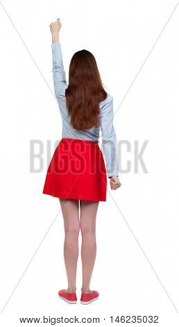 Back view of woman. Raised his fist up in victory sign. Long-haired brunette in red skirt held up his hand with his fists.