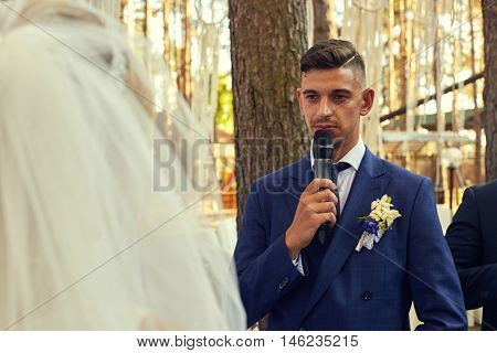 Groom looks at a bride with love while telling his oath. Oath of the groom and bride during wedding registration.