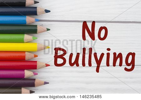 Pencil Crayons with text No Bullying with weathered wood background
