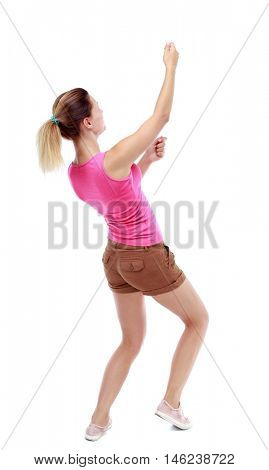 back view of standing girl pulling a rope from the top or cling to something. Isolated over white background. Sport blond in brown shorts hanging on a rope.