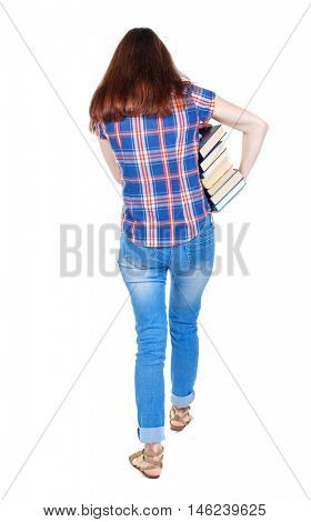 Girl comes with stack of books. back side view. Girl in plaid shirt holding out arm textbooks.