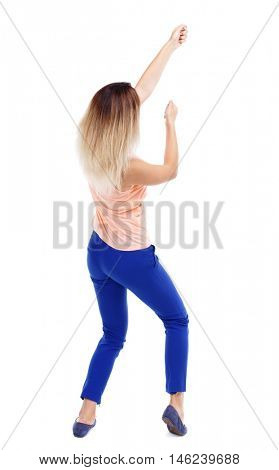 back view of standing girl pulling a rope from the top or cling to something. backside view of person. Isolated over white background.