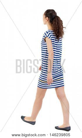 back view of walking curly woman. Swarthy girl in a checkered dress goes diagonally.