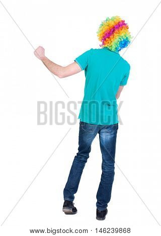 back view of dancing young beautiful man in clown wig. Curly man in a turquoise sweater and clown wig waving hands.