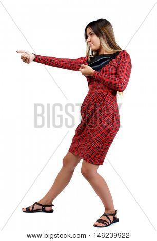 back view of standing girl pulling a rope from the top or cling to something. girl in red plaid dress stands sideways and pull the rope from the side.