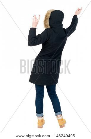 Back view woman in winter jacket Balances waving his arms. Standing young girl in parka. girl in warm winter jacket black dancing.