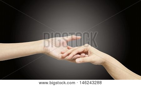 Closeup woman hand hold another woman hand for console and encourage in tender emotion isolated on black background