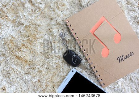 Notebook with car key and mobile phone on brown shaggy carpet