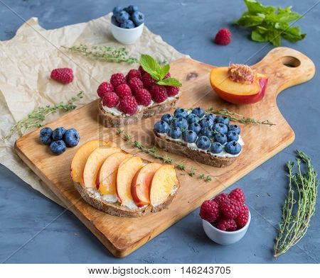 Sandwiches with mild cream cheese and different berries on wooden cutting board
