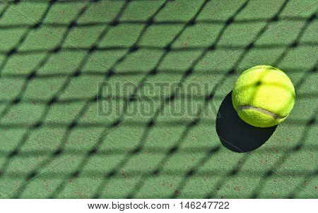 tennis ball in net shadow on court