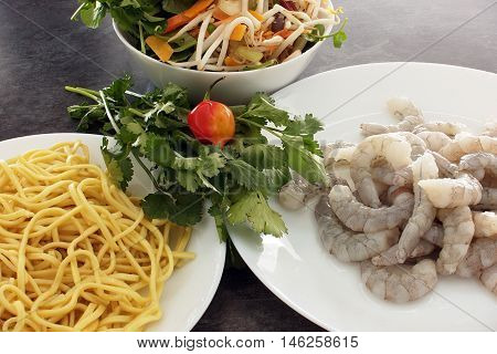 Fresh noodles and raw king prawns for prawn laksa soup on plates. Vegetable mix in bowl.