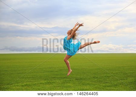 Young woman in blue dress jumping on grass over gloomy cloudscape