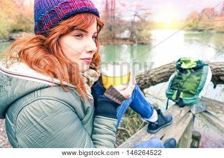 Red hair woman sitting by river at sunset - Pretty girl relaxing with tea cup at lakeside on winter trekking weekend - Peaceful concept of healthy lifestyle with autumn colors - Soft vintage filter