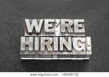 we are hiring exclamation made from vintage metallic letterpress blocks on dark background