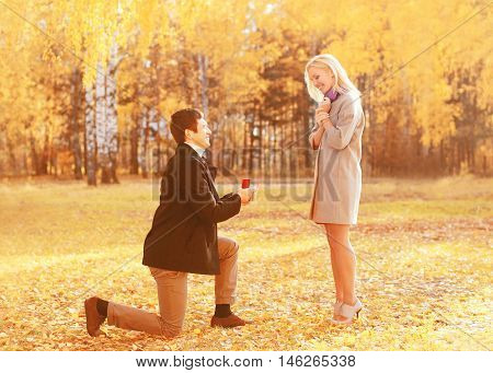 Love, Relationships, Engagement And Wedding Concept - Kneeled Man Proposes A Woman To Marry, Red Box