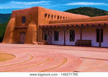 Southwestern style adobe building taken from a courtyard with mountains beyond in Santa Fe, NM