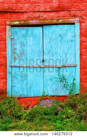 Abandoned boarded up colorful southwestern adobe building beside a lush garden