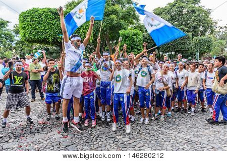 Antigua Guatemala - September 14 2015: Local students cheer & run in streets with Guatemalan flags & lit torches while blowing whistles & horns during Guatemalan Independence Day celebrations