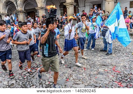 Antigua Guatemala - September 14 2015: Locals run in streets with Guatemalan flags & lit torches while blowing whistles & horns during Guatemalan Independence Day celebrations