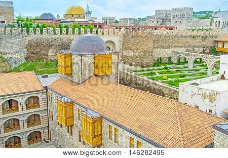 The stone rampart hides the renovated mosque with the golden dome and separates the buildings and gardens of the different levels of the Rabati fortress Akhaltsikhe Georgia.