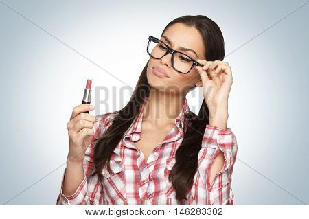 Attractive woman geek holding lipstick in hand